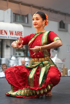 A Bharatanatyam dance in Toronto expressing a part of a play with hand and facial gesture, in the dance's distinctive bent leg position.