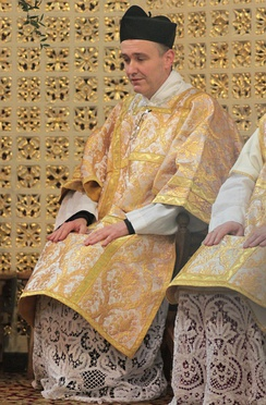 A deacon in a dalmatic and a biretta