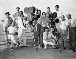 Some of Welles's film crew at the top of Sugarloaf Mountain, Rio de Janeiro, in early 1942. Standing, from left: John M. Gustafson, Technicolor technician; Dante Orgolini, Mercury public relations; Jose Santos (perhaps Orlando Santos, assistant from the Cinédia studio); Duke Greene, Technicolor cinematographer;  Sidney Zisper, Technicolor technician; Henry Imus, Technicolor camera operator; Ned Scott, still photographer; Joseph Biroc, camera operator (black-and-white); Robert Meltzer, screenwriter and second unit director; Willard Barth, assistant cameraman; Leo Reiser, location production coordinator. Seated at left: James Curley, grip. Crouching: Harry J. Wild, cinematographer (black-and-white).
