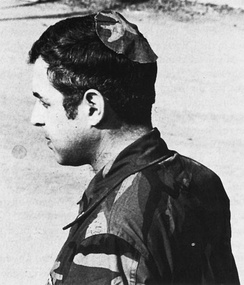 Jewish chaplain Rabbi Arnold Resnicoff wears a kippah/yarmulke made from a piece of a Catholic chaplain's camouflage uniform after his own head covering had become bloodied when it was used to wipe the face of a wounded marine during the 1983 Beirut barracks bombing.
