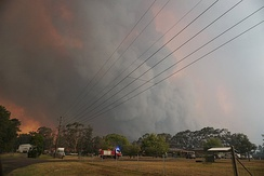Fire crews move in to protect properties from an out-of-control bushfire in South West Sydney