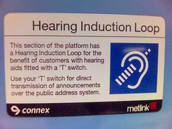 "A sign in a train station explains that the public announcement system uses a ""Hearing Induction Loop"" (audio induction loop). Hearing aid users can use a telecoil (T) switch to hear announcements directly through their hearing aid receiver."