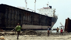 Workers drag steel plate ashore from beached ships in Chittagong, Bangladesh