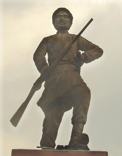 A cement statue depicting a man with a moustache holding a rifle in one hand and a stick in another, wearing traditional clothes. He stands on a polished stone pedestal.
