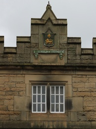 The 1852 extension includes a relief carving of the coat of arms of Lancaster.