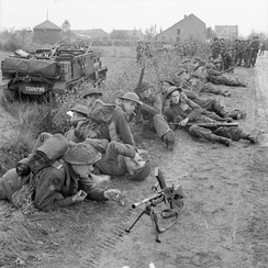 Universal Carriers and infantrymen of the 8th Battalion, Royal Scots pause during the attack by 15th (Scottish) Division on Tilburg, 27 October 1944.