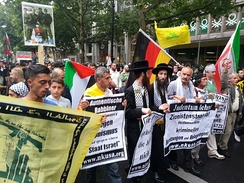 Two Neturei Karta members join in a large anti-Israel demonstration in Berlin, alongside Iranian and Hezbollah flags.