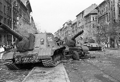Two Soviet ISU-152 assault guns positioned in a street in Budapest 8th District. An abandoned T-34/85 stands behind them