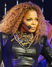 Janet Jackson with big curly hair looking to her left