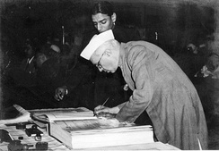 A bespectacled Jawaharlal Nehru bending over a large book