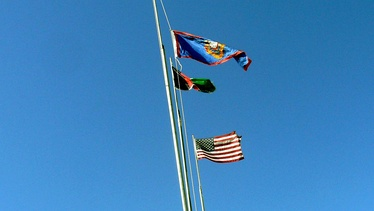 The Lincoln and Welland camp flag, Afghan flag and the American flag in Afghanistan