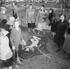 Liberated women inmates gaze at the naked body of a child who has died of starvation