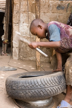 Above:A boy repairing a tire in Gambia.