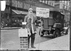 A man dressed as Santa Claus fundraising for Volunteers of America on the sidewalk of street in Chicago, Illinois, in 1902. He is wearing a mask with a beard attached.