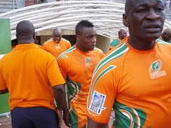 A close-up shot of the Ivory Coast players, in their country's orange jerseys, entering the field from the dressing room tunnel