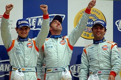 The drivers of the No. 009 Aston Martin DBR9 celebrating a first-place finish in GT1