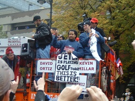 "Group of men on a raised platform. One holds a sign that reads ""JETER is playing GOLF today"" and ""THIS IS BETTER!"""