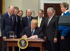 President Trump signs Space Policy Directive 1 on December 11, 2017, with astronauts Harrison Schmitt, Buzz Aldrin, Peggy Whitson, and Christina Koch looking on.