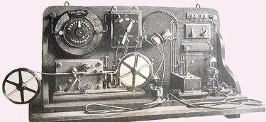 "One of Marconi's first coherer receivers, used in his ""black box"" demonstration at Toynbee Hall, London, 1896. The coherer is at right, with the ""tapper"" just behind it, The relay is at left, batteries are in background"