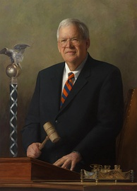 Hastert's official portrait as Speaker, painted by Laurel Stern Boeck. The mace of the United States House of Representatives is in the background, and the historic House silver inkstand in the foreground. This portrait was unveiled in 2009.[233]