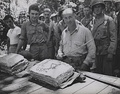 William W. Stickney cuts a Thanksgiving cake with a Japanese officer's sword at Guadalcanal, as hungry Leathernecks look on