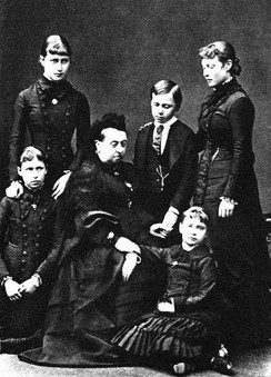 Ernest in early 1879 with his grandmother Queen Victoria and sisters Victoria, Elizabeth, Irene and Alix two months after the deaths of their mother and his youngest sister.All are wearing mourning clothes.