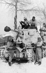 Snow-camouflaged German Marder III jagdpanzer and white-overalled crew and infantry in Russia, 1943