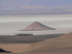 """Cono de Arita"" at the dry lake Salar de Arizaro on the Atacama Plateau, in northwestern Argentina. The cone itself is a volcanic edifice, representing complex interaction of intrusive igneous rocks with the surrounding salt.[9]"