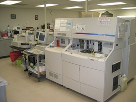 Clinical laboratory in a hospital setting showing several automated analysers.
