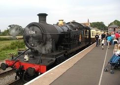 A black steam engine (number 5224) with passengers alighting at a station platform.