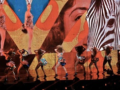 "Beyoncé performing ""Grown Woman"" with her female background dancers, wearing animal printed dresses. The projection behind them showed African-inspired video projection."