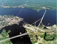 Aerial view of New Bern (center left) showing the confluence of the Trent (bottom center) and Neuse (left to right) rivers.  East is up.  The two larger bridges carry U.S. 70, U.S. 17, and NC 55, bypassing New Bern to the south through the unincorporated community of James City.  The smaller bridge crossing the mouth of the Trent River is Front Street, while the smaller bridge crossing the Neuse is a railroad bridge.