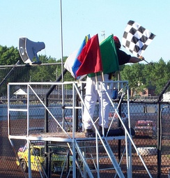 The flagman displaying the chequered flag with a complete set of stockcar racing flags