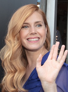 A photograph of Amy Adams, smiling and waving at the camera
