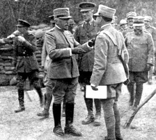 Generalissimo Luigi Cadorna, (the man to the left of two officers to whom he is speaking) while visiting British batteries during World War I