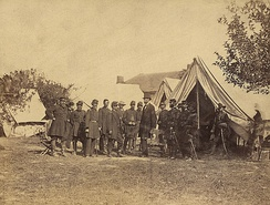 Lincoln among a group of soldiers in a military camp