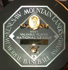 "A black circle with an octagonal silver plaque in the middle. The edge of the plaque reads ""KENESAW MOUNTAIN LANDIS MEMORIAL BASEBALL AWARD"". In the middle of the octagon is a baseball diamond which contains, from the top, Judge Landis' face in gold, ""Most Valuable Player"", the winner's league, his name in a gold rectangle, and his team."