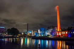 A 2015, night picture of the Tammerkoski rapids in Tampere. The Festival of Light has just opened and an old, large factory chimney is lit in red on the right side of the rapids and contrasts with the blue lighting of the trees beneath it. The array of colours is reflected by the water of the rapids.