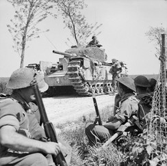 A Churchill tank halts near infantrymen of the 1st Battalion, London Irish Rifles, part of 167th Brigade of 56th (London) Division, near Tanara, Italy, April 1945