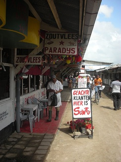 Butcher market in Paramaribo with signs written in Dutch.