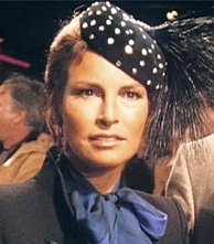 Welch in blue scarf and high-collared gray jacket, with polka-dot feathered cap.