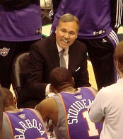 A man, wearing a black suit and a gray tie, is surrounded by basketball players as he talks to them.
