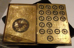 book sized metal machine with large dial left page and nineteen small dials right page