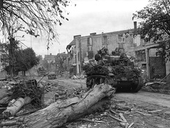 M5A1 Stuart Light Tank passes through the wrecked streets of Coutances.