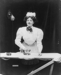 A domestic servant ironing a lace doily with GE electric iron, ca. 1908