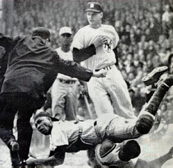 Howard during a collision at home plate, 1961 World Series. The umpire is Jocko Conlan.