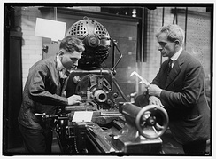 "A trainee machinist and his supervisor wear neckties while at work in a machine shop in 1917. In a modern setting, ""professional"" dress would likely be superseded by more practical clothing due to the risk of a dangling necktie becoming entangled in moving machinery."