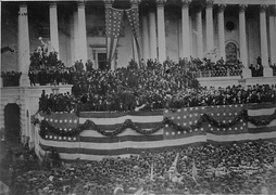 Photograph of a crowd in front of Capitol building decorated with patriotic bunting