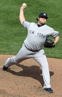 "A man in a grey uniform with ""NEW YORK"" written in navy letters prepares to throw a ball."