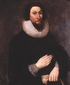 A painting of a man with a stern expression on his face, wearing very dark clothing so that his pale hands show boldly. His hands are placed in front of him, separately, one above the other.